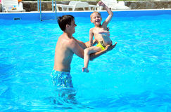 Fun in pool. Father fling in  his little son in the pool, they are smiling, they are happy Stock Image