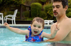 Fun in the pool 2. A father and a toddler daughter are having fun in the swimming pool on a summer evening Royalty Free Stock Photo