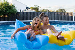 Fun in the pool. Girls floating together, laughing, and having fun in the swimming pool Stock Image
