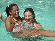 Fun in the Pool. A picture of two friends laughing and having fun in the swimming pool Stock Image