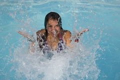 Fun in the pool. A playful teenage girl splashing water in a swimming pool Royalty Free Stock Images