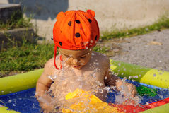 Fun in the pool. A little boy playing in the children pool on the garden. Happy childhood concept Stock Photo