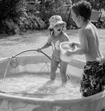 Fun in the Pool. Two happy, smiling children having fun in a kiddie pool with bucket and water hose Stock Photo