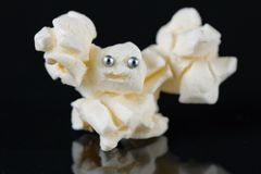 Halloween popcorn animal. Fun popcorn buddah with pinhead for eyes on black background stock photos