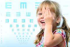 Fun portrait of kid testing vision. Close up fun portrait of little girl testing eye sight.Vision test chart in background Stock Image