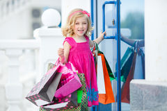 Fun preschool girl walking with bags. Stock Photo