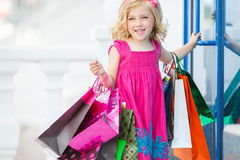 Fun preschool girl walking with bags. Royalty Free Stock Photo
