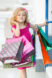 Fun preschool girl walking with bags. Royalty Free Stock Photography