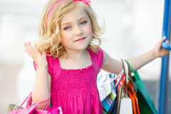 Fun preschool girl walking with bags. Stock Photos