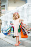 Fun preschool girl walking with bags. Royalty Free Stock Photos