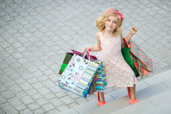 Fun preschool girl walking with bags. Stock Images