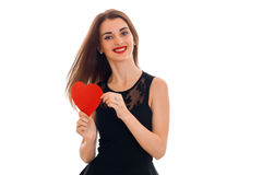 Fun pretty girl in black dress holding a card in the form of a red heart. Isolated on white background Royalty Free Stock Image