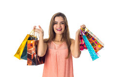 Fun pretty girl looks straight and keeps two hands many colored packages isolated on white background Royalty Free Stock Image