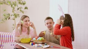 Fun and radiant family of mom, dad and daughter Caucasian appearance, have fun before Easter holding Easter eggs damage