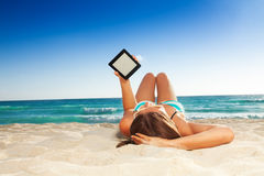 Fun reading on the beach. Beautiful young woman laying on white sand beach and reading from her tablet pc Stock Photos