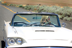 Fun Ride. A pretty lady in a Classic 1960 shiny white Ford Thunderbird Convertible enjoying a ride on a country road out in the middle of no where. Shallow depth stock images