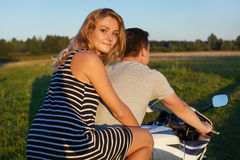 Fun ride. Young couple riding a motorbike. Handsome guy and pretty woman on the motorcycle. Young riders enjoying themselaves on t. Fun ride. Young couple riding Stock Photography