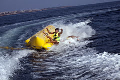 Fun riding banana boat. Group of young people having fun riding banana boat Royalty Free Stock Photos