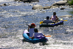 The fun of the river. 2 young couples river rafting Royalty Free Stock Photos