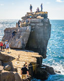 Fun on the Rock. Families having fun rock climbing by the sea. This is Pulpit Rock located at Portland Bill on the south coast of the UK Royalty Free Stock Photography