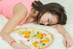 Girl with pizza. Fun sad overeat girl lying with pizza pieces Royalty Free Stock Images