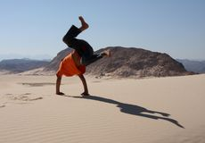 Fun in the sand. Young boy having fun doing cartwheels in the sand royalty free stock photos