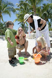 Fun in sand. Two women and children playing in the sand on their vacation Royalty Free Stock Photography