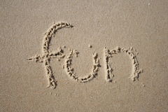Fun in the sand. Fun written in the beach sand stock photography