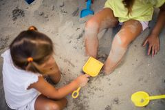 Fun in sand. Two little girls playing in sand together. Close up royalty free stock images