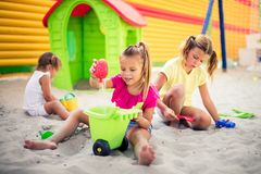 Fun at sand. Three little girls playing in sand on playground stock photo