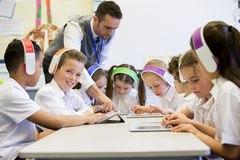 Fun at School. Group of children wearing colourful wireless headsets while working on digital tablets, the teacher can be seen supervising the students in the Stock Photos