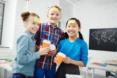 Fun in school. Laughing classmates with drinks playing name game during lunch break in school Stock Image