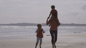 Fun by the sea. A happy young family of three walk along the water's edge on the beach together. The mother is carrying her son on her shoulders as she watches stock video footage
