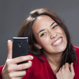 Fun selfie with toothy smile from cute young multiethnic girl. Selfie concept - Adorable female teenager laughing for selfie portrait on cell phone Stock Photo