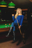 Fun sexual lady posing on pool table with the cue and ball in ha Stock Photography