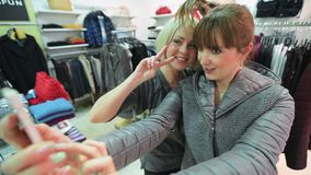 Fun shopping and selfie in clothing store. Two joyful girls shopping in a clothing store doing a selfie stock footage