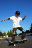 Fun on Skateboard. Teenage boy having fun skateboarding on a parking lot on a sunny day Stock Image