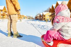 Fun sled ride with father. Unrecognizable men dragging sled with his little daughter along snowy road on beautiful winter day out of town Royalty Free Stock Images