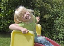 Fun on a slide. Young happy girl on a slide Royalty Free Stock Image