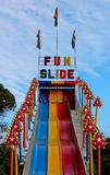 Fun slide ride at outdoor carnival. Outdoor amusement park fun slide against blue sky Royalty Free Stock Photography
