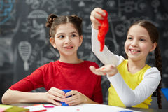 Fun with slime. Playful girl having fun with red slime while her friend looking at this stock photo