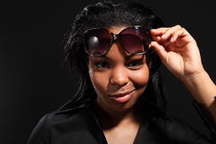 Fun smile by young woman wearing sunglasses. Fun smiling headshot from beautiful young black woman, holding dark sunglasses on her head and wearing black shirt Stock Images