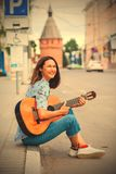 Fun smiling woman with a guitar sits on the curb Royalty Free Stock Photo