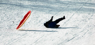Fun in the snow. A man falling off the sledge Stock Photography