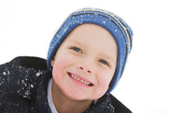 Fun in the snow. A child smiles gleefully as he has the time of his life playing in the snow stock photography