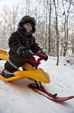 Fun on snow sledge. Young boy having fun going dowbhill on a snow sledge Stock Photography