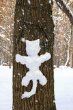 Fun snowman on pine trunk in the form of cat, winter snowfall day. Stock Photos