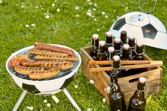 Fun soccer ball styled BBQ for the World Cup. With assorted sausages grilling over the fire and a crate of bottled beer in a green spring meadow stock photography