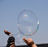 Fun with soap bubbles. Kids trying to burst the soap bubbles Stock Image