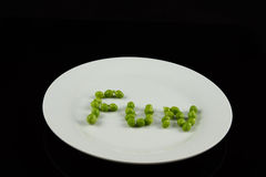 Fun spelled with peas. On a white plate Royalty Free Stock Photo